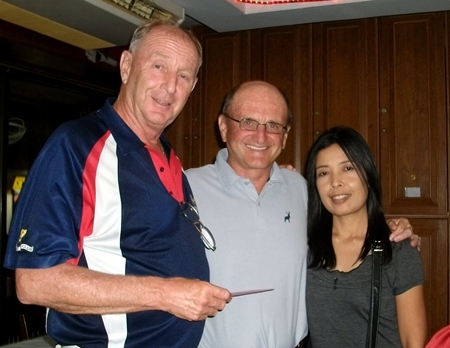 Colin Davis (left) presents a prize to Sunday A Flight winner John Stewart (center) and his wife.