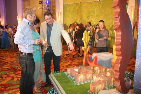 Party-goers view a scale model of the Seven Seas project.