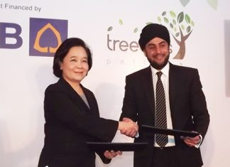 Kluaymai Thephasadin Na Ayutthaya, Vice President Siam Commercial Bank (left), providers of project finance for Treetops, exchanges contracts with Prab Thakral, founder of Thai-based Thakral Land Ltd. (right) at the press conference held Nov. 24.