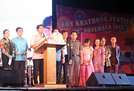 Mayor Itthiphol Kunplome announces the start of this year's Loy Krathong festivities at Bali Hai, as high ranking police officials along with TAT staff and city councilors cheer him on.