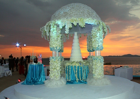 A beautiful sunset provides the backdrop for the virgin wedding cake.