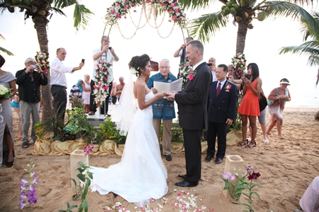 The beach of the Pinnacle Resort provides a picturesque romantic backdrop as Father Fred Doell conducts the wedding ceremony.