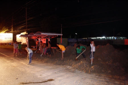 Workers hurriedly remove the dangerous pile of dirt before anyone else is injured.