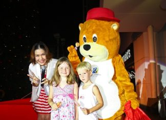 Mr. Happiness Bear hands out treats to young children during the official Christmas and New Year's launch at the Royal Garden Plaza.