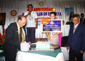 Jin Srikasikorn cuts the birthday cake for the Rotary Club of Pattaya's 40th anniversary.
