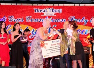 Brenda Foster from the UK is thrilled as she receives the grand prize of two round-trip air tickets Bangkok - Chiang Mai, courtesy of Thai Airways International including 2 nights stay at D2 Hotel Chiang Mai from Chatchawal Supachayanont (3rd right), GM of Dusit Thani Pattaya during the Mardi Gras New Year's Eve party held at the resort.