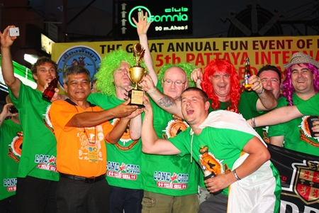 """Jamlong Passara (2nd right), president of Rotary Club Pattaya 2012-2013, presents the """"wooden spoon"""" trophy to Murphy's Law for finishing last in the Pattaya International Bed Race 2013."""
