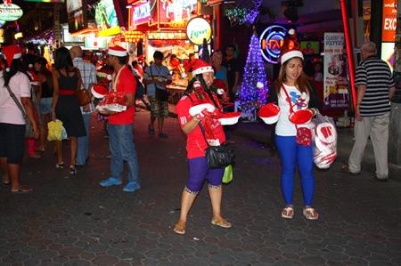Vendors line Walking Street, selling Christmas hats.
