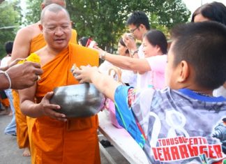 Abbot Pisan Jariyaphiwat leads more than 50 monks to accept alms from large groups of worshippers at Chaimongkol Temple in South Pattaya.