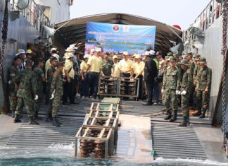 EGAT officials and Royal Thai Marines throw overboard high-voltage insulator bulbs to be used to form a foundation for artificial coral reefs.