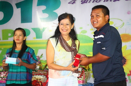 Education Department director Jintana Maensurin (left) presents gold to a lucky employee during the New Year's party at Pattaya Youth stadium.