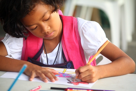 This young girl is full of concentration, trying not to stray outside the lines when coloring her favorite cartoon.