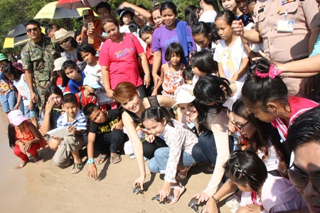 Children in Sattahip are treated to a visit from Miss Thailand Universe 2012 Vanessa Muangkhorat whilst releasing turtles into the sea.