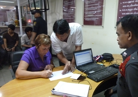 Russian victim Nina Vitiutneva fills out a police report after being robbed on the ocean side of Pratamnak Hill.