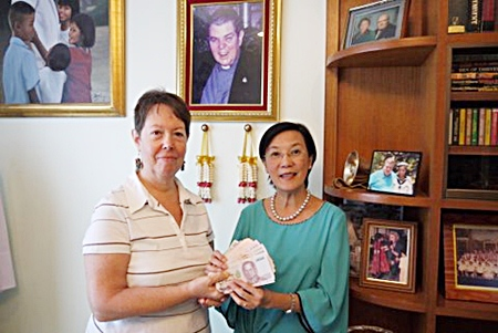 Judith hands the money donated by PCEC members to Toy at the Pattaya Orphanage.