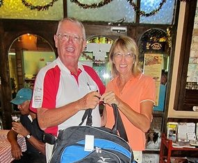Carole Kubicki (right) is presented with the MBMG Golfer of the Month award by Dick Warberg.