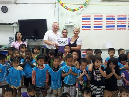 Event organisers Eva Johnson and Earl Brown present a record amount of 76,400 baht to the Hand to Hand Foundation following November's 1st anniversary party.