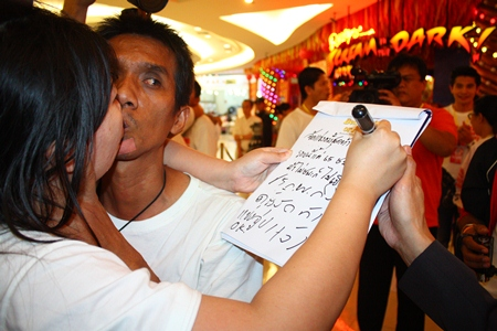 Laksana Tiranarat (left) writes a message to her husband Ekachai to encourage him to continue standing and kissing beyond 50 hours.