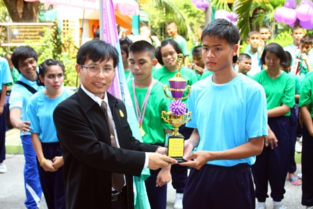 Suphamit Srikanthamakul, deputy director of the Chonburi Office of Primary Education Region 3, presents the winning cup to the blue team.