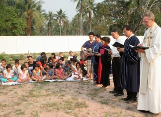 Priests conduct the consecration ceremony as children join in singing hymns.