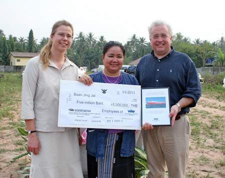 Piangta Chumnoi holds the 5 million baht cheque that was presented to her by Trond Tønjum and Jesse Linde of Wallenius Wilhelmsen Logistics.