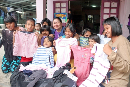 Children are thrilled with the gift of new clothing brought by their benefactors.