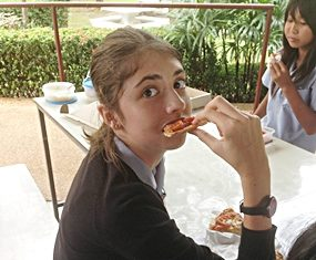 A GIS student tucks into her pizza.