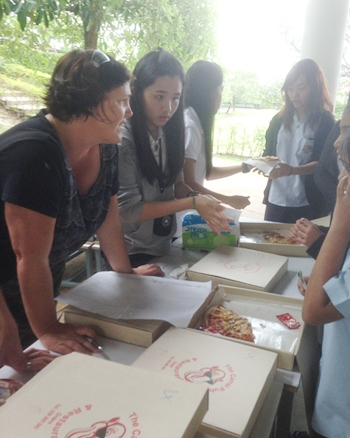 IB CAS coordinator Ms Morris helps students dish out the pizza.