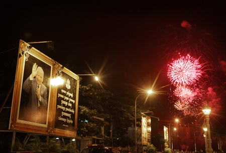 Fireworks explode next to a poster of Cambodia's former King Norodom Sihanouk as his body is cremated in Phnom Penh. (AP Photo/Wong Maye-E)