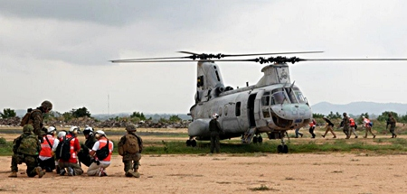 Evacuees are led to a U.S. Marine Corps CH-46E Sea Knight helicopter while conducting a multinational emergency evacuation drill Feb. 17 in Pattaya, during exercise Cobra Gold 2013. Military members from Thailand, Japan, Indonesia, and Malaysia worked alongside U.S. Marines and sailors of the 31st Marine Expeditionary Unit to process multinational citizens through security and screening stations before evacuating them via helicopter. (130217-M-IM838-096)