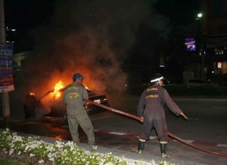 Firefighters work to extinguish the blazing taxi.
