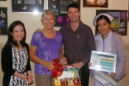 Phyathai Sriracha Hospital's International Marketing Director, Gavin Wadell, presents PCEC Chair Pat Koester with a gift hamper recognising the long cooperation between the hospital and Pattaya City Expats. Dr Nalinee and Nurse Wanvisa (who provided much appreciated blood pressure checks) look on.