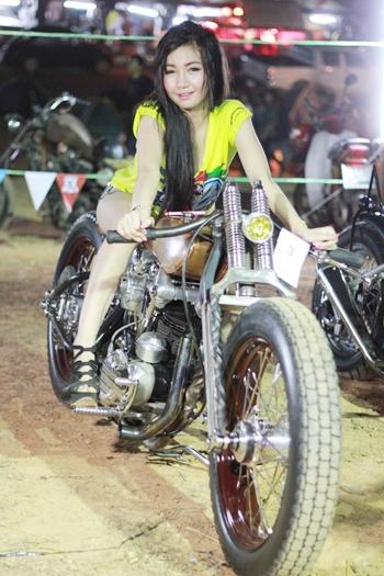 A beautiful model poses on a retro bike.