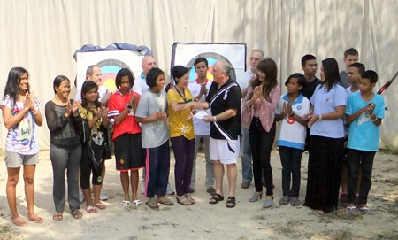 Allan Jones (center-right) presents a cheque for 25,000 baht to Khun Toy of the CPDC.