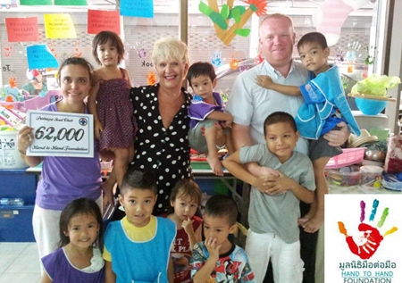 Pattaya Soul Club founders Earl Brown and Eva Johnson (standing rear center) present a cheque for 62,000 baht, money raised from the March Soul Night, to representatives and children at the Hand to Hand Foundation in Pattaya.