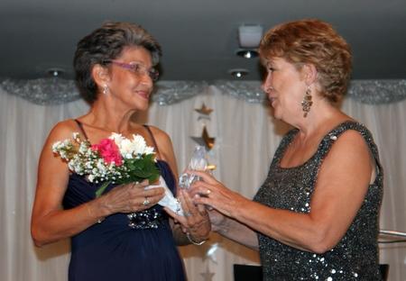 Founding member Pat Burbridge (left) receives a token of appreciation from Ann Winfield.