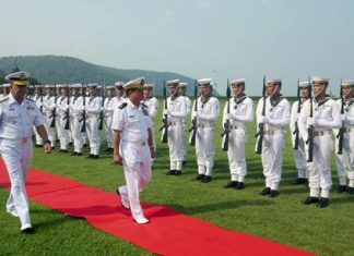 Myanmar's top naval commander, Rear Adm. Tulataed Chuay walks the red carpet to inspect a Thai Marine Corps honor guard of 100 sailors.