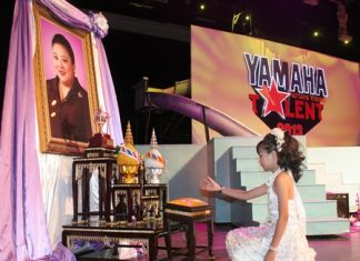 "Phakhaporn ""N'Om"" Sukhpanit, 11, picks up her trophy from in front of the HRH Princess Soamsawalee royal image."