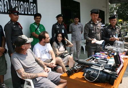 Police bring out for the press the 3 foreigners accused of pornography, along with tools of the trade allegedly confiscated from their house.