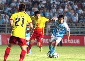 Pattaya United's Anuwat Inyin (right) dribbles past Osotspa defenders during the second half of the Thai Premier League match at the Nongprue Stadium, Sunday, March 10.