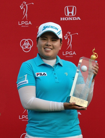 / South Korea's Inbee Park holds up the champion's trophy after winning the 2013 Honda LPGA Thailand Championship at Siam Country Club, Pattaya, Sunday, Feb. 24.