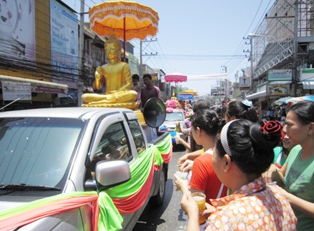 Citizens and tourists pour water on the Buddha statues and receive blessings in return from the monks in the parade.