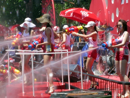 Spy girls spray water on people from the Hard Rock Cafe stage.