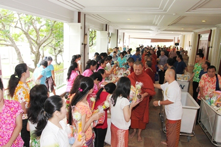 The foyer outside the Dusit Thani Pattaya's Napalai Convention Hall is filled with hotel guests and staff who make merit by giving donations to the twenty-nine monks, who will later distribute the goods to among the community.