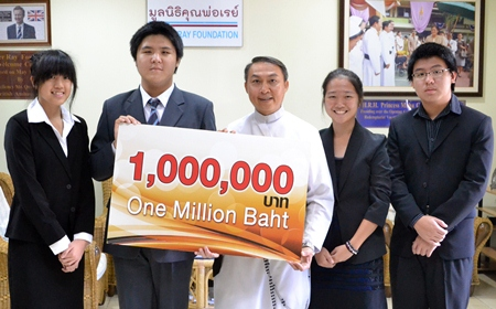 Father Peter accepts the cheque from the Bangkok students.