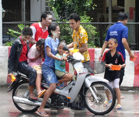 Four people on a single motorcycle, including 3 children, and not one person wearing a helmet - all making for a good example of what NOT to do during the Songkran holidays.