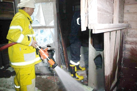 Firefighters move in to extinguish the final embers after smoking in bed caused a fire that destroyed a house in Sattahip.