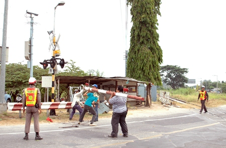 City workers repair the train-crossing gate damaged by a speeding car on Soi Siam Country Club.