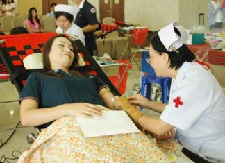 Nurse Kotchakorn Auamsamang (right), chief of the blood donation unit at Sriracha's Ratchathewi Hospital, Sriracha, attends to a donor.