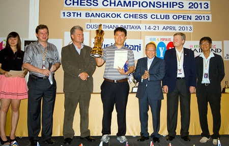 Australia's Zhao Zong-Yuan (center) holds up the champion's trophy after winning the 2013 Thailand Open chess title at the Dusit Thani Pattaya resort, Sunday, April 21.
